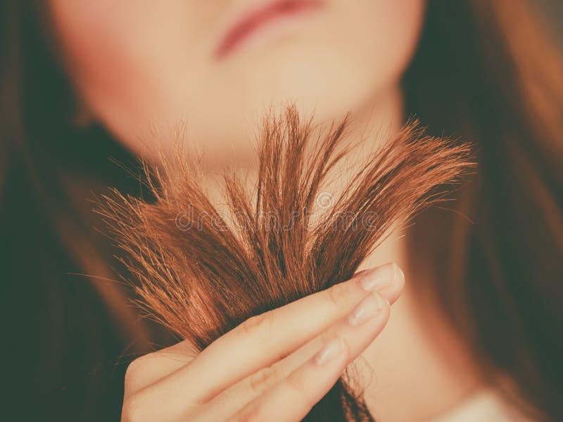 看她的干毛发末端的担心的妇女 免版税库存照片
