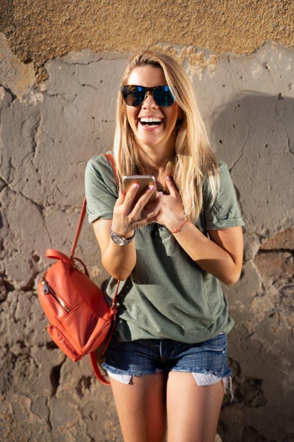看她的手机和拿着饮料的美丽的微笑的妇女 图库摄影