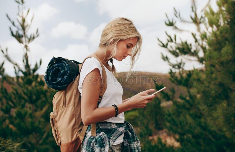 看她的手机的妇女旅行家的侧视图 免版税图库摄影