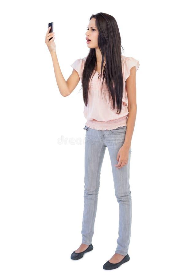 看她的手机的懊恼妇女 免版税库存照片