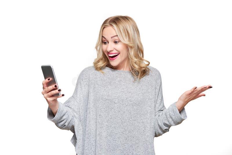 看她的手机的激动的年轻女人怀疑地微笑和庆祝 妇女读书正面短信 免版税图库摄影
