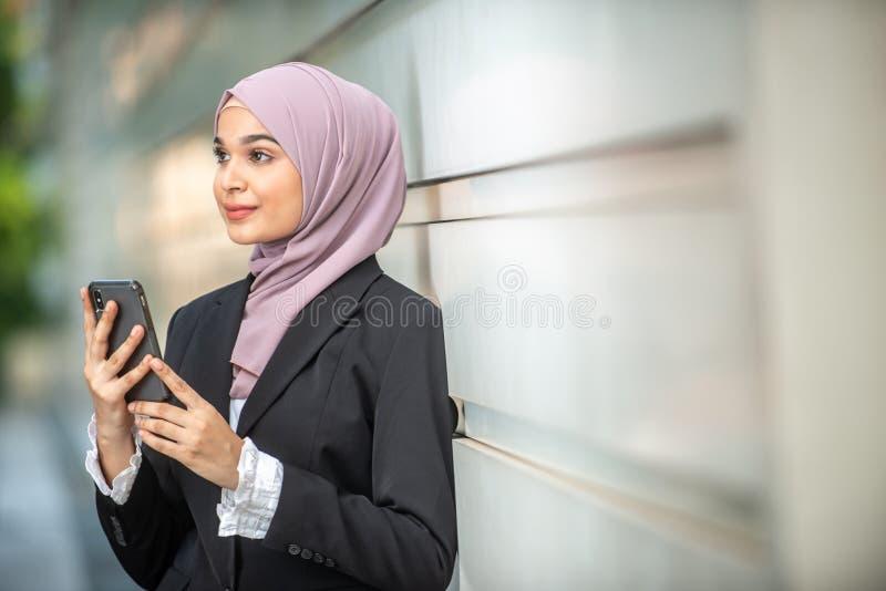 看她的智能手机的年轻女性回教企业家 免版税图库摄影