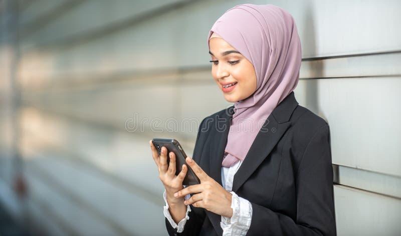 看她的智能手机的年轻女性回教企业家 免版税库存照片