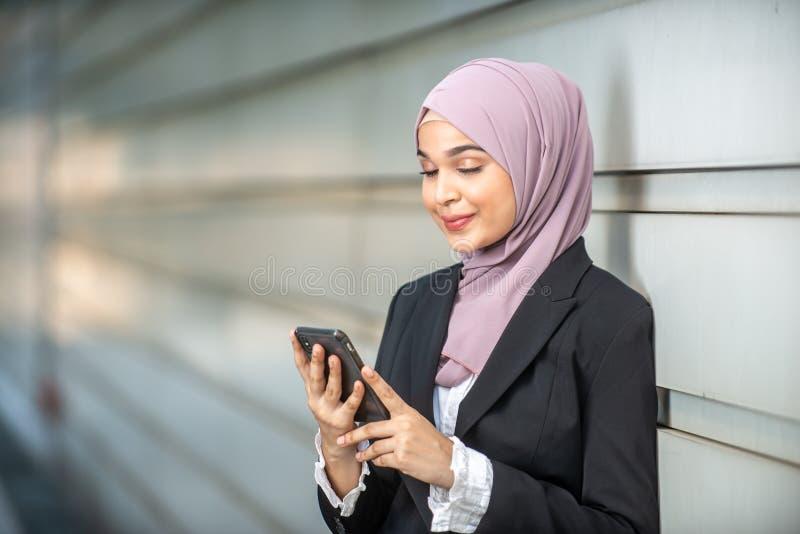 看她的智能手机的年轻女性回教企业家 库存照片
