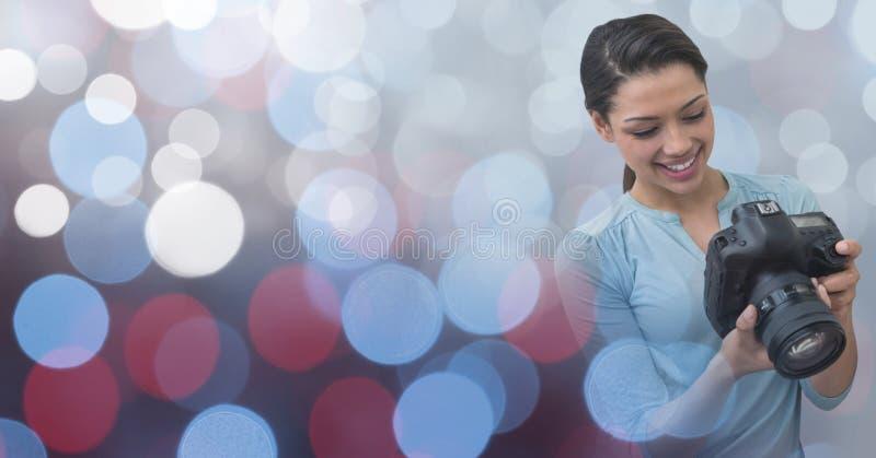 看她的照相机的摄影师反对发光的背景 库存图片