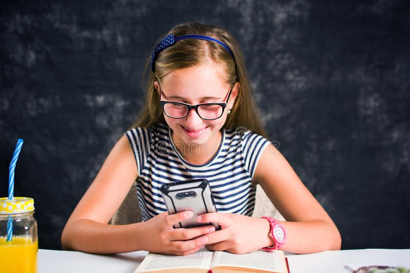 看她电话和微笑的青少年的女孩 免版税库存照片