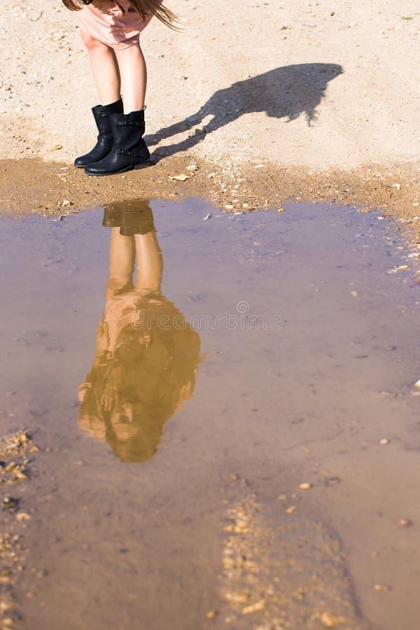 看她自己的女孩反射水坑桃红色礼服起动 免版税库存照片