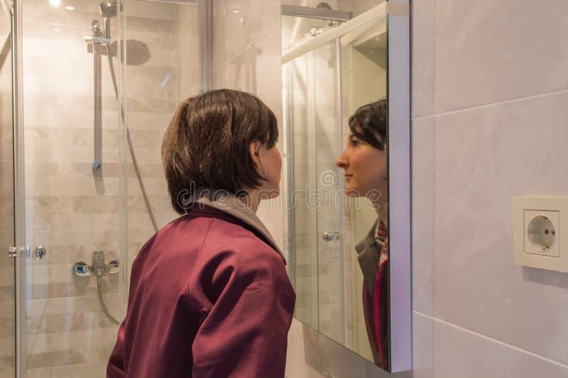 看她自己的妇女在镜子在卫生间里 免版税图库摄影