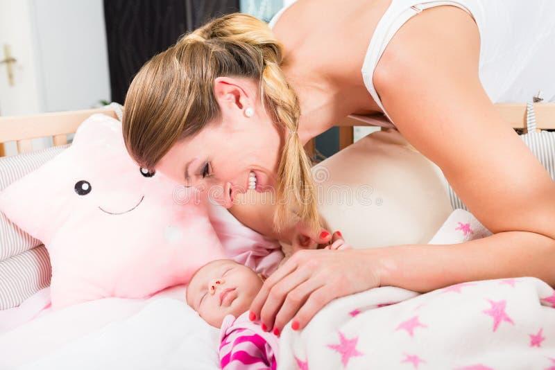 看婴孩睡觉的愉快的母亲 免版税图库摄影