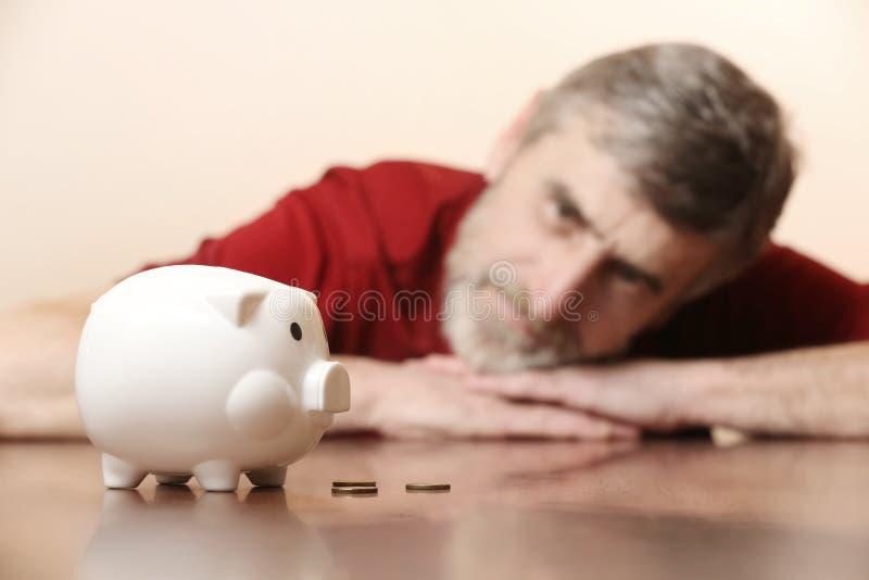 看存钱罐的老人 免版税库存照片