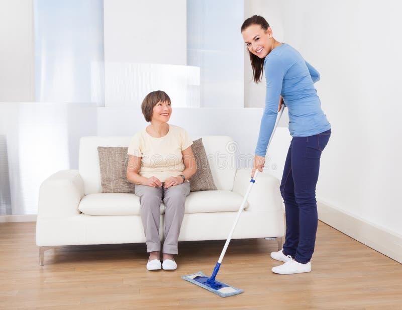 看守者清洁地板,当妇女坐沙发时 免版税库存照片
