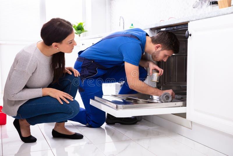 看安装工的妇女修理洗碗机在厨房里 图库摄影