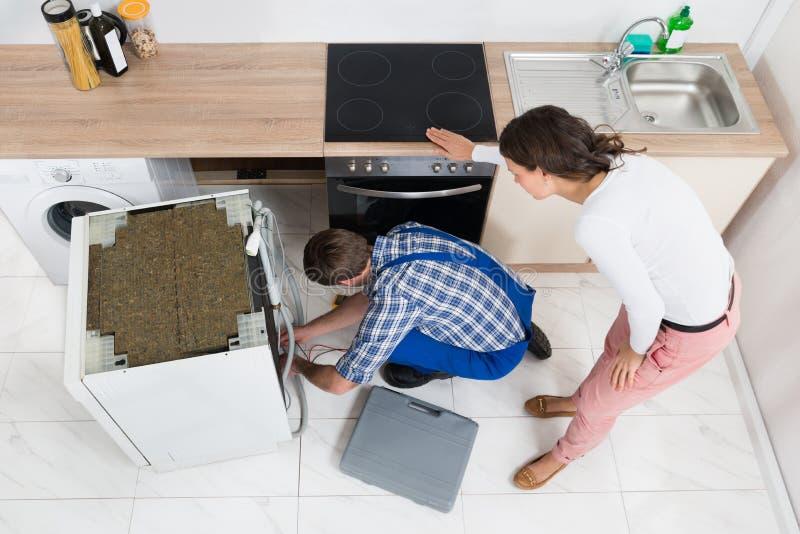 看安装工的妇女修理洗碗机 免版税库存图片