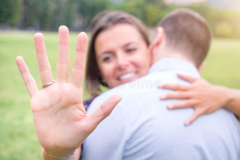 看定婚戒指的微笑着妇女在提案以后,当古芝时 免版税库存图片
