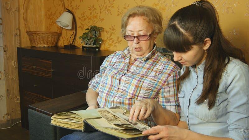 看家庭照片册页的老和少妇 库存图片
