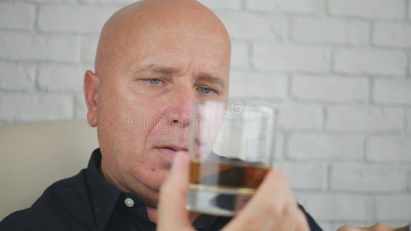 看对一块玻璃的商人用威士忌酒和抽烟的雪茄 图库摄影