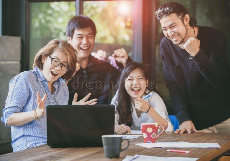 看对便携式计算机的亚洲自由职业者的配合幸福情感在家庭办公室 免版税库存图片