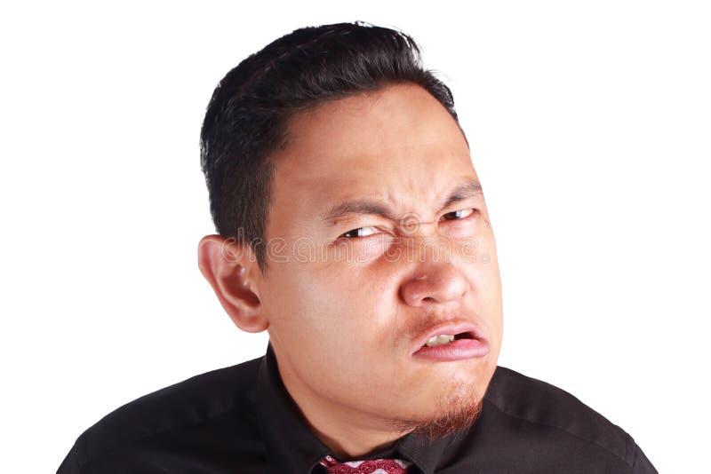 看对充满愤怒的照相机的玩事不恭的亚洲商人 库存照片