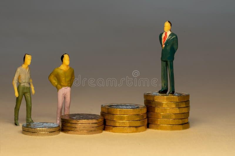 看对商人身分的一般人在增长的堆金币顶部 企业事业概念 免版税库存照片