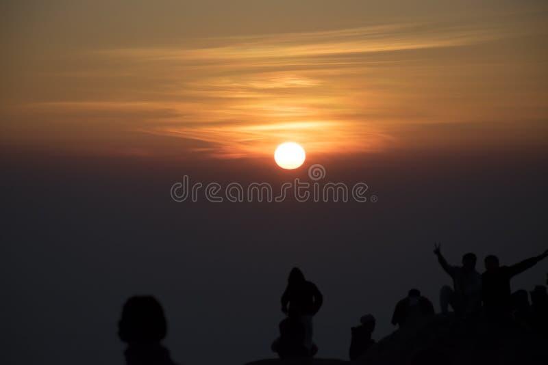 看对在山的日落的剪影人为背景 免版税库存图片