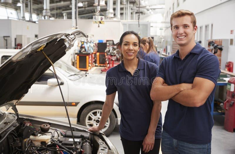 看对在汽车旁边的照相机的两位学徒技工 免版税库存照片