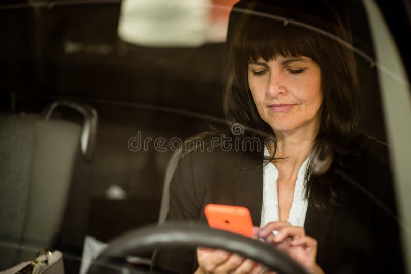 看对在汽车的电话的成熟的商业妇女 库存图片