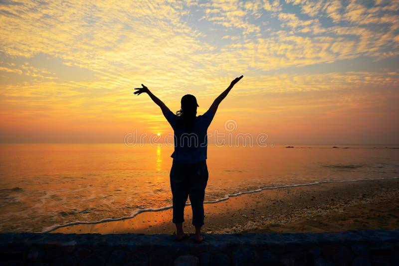 看对在海滩的日落的妇女 免版税库存照片