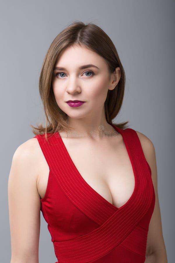 看对在灰色背景的照相机的红色礼服的美丽的妇女 免版税库存照片