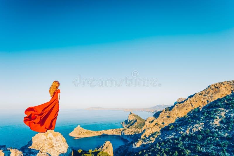 看对山海的红色礼服的年轻美女 免版税库存照片