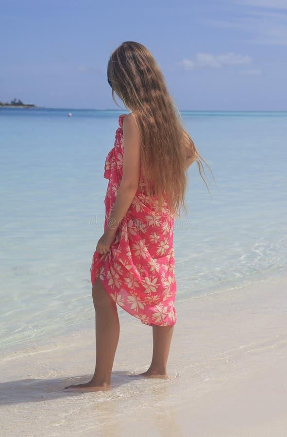 看对海滩的海洋的女孩 免版税库存照片