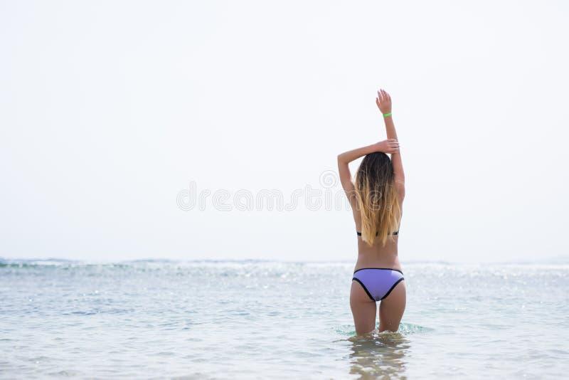 看对海洋的年轻俏丽的妇女室外夏天画象热带海滩,享用她的自由和新鲜空气在比基尼泳装 免版税库存图片