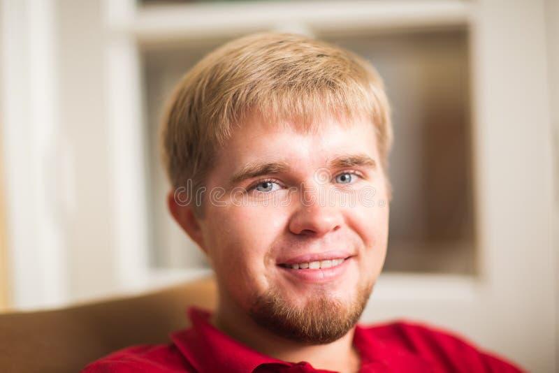 看对照相机的一个英俊的白肤金发的人的画象 免版税库存图片