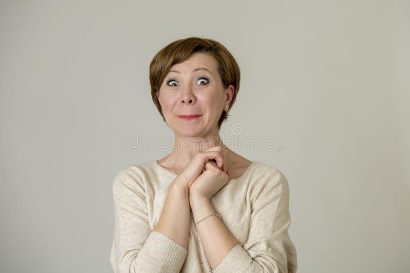 看对照相机的年轻愉快和惊奇的红色头发妇女高兴吃惊和在惊奇面孔表示隔绝在灰色b 库存照片