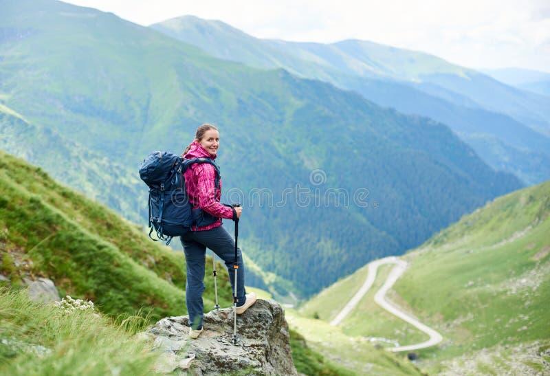 看对照相机的正面微笑的女性游人,当攀登在绿色落矶山脉时的一个岩石 库存照片
