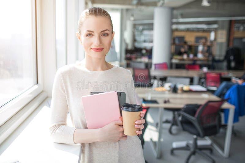 看对照相机的穿着体面的女孩的图片 她在一只手和一杯咖啡上在其他上拿着笔记本 库存照片