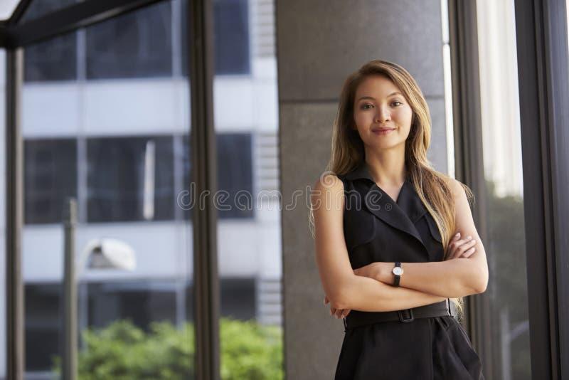 看对照相机,胳膊的年轻亚裔女实业家横渡 库存照片