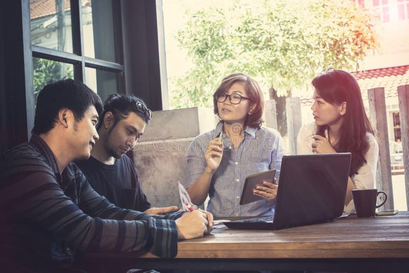 看对膝上型计算机com的亚洲自由职业者的配合幸福情感 库存照片