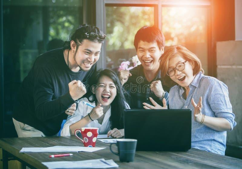 看对膝上型计算机com的亚洲自由职业者的配合幸福情感 免版税库存照片