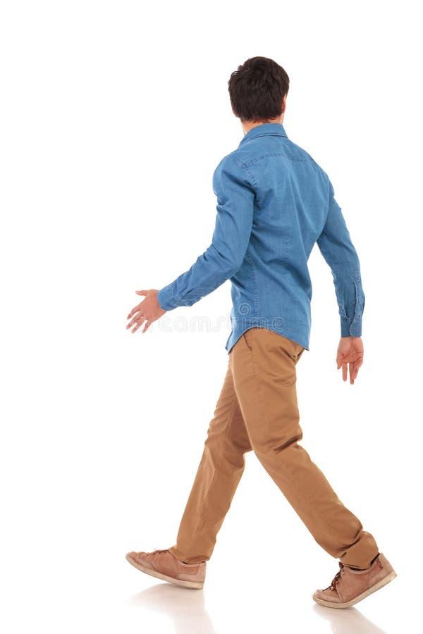 看对边的一个走的偶然人的背面图 免版税库存照片