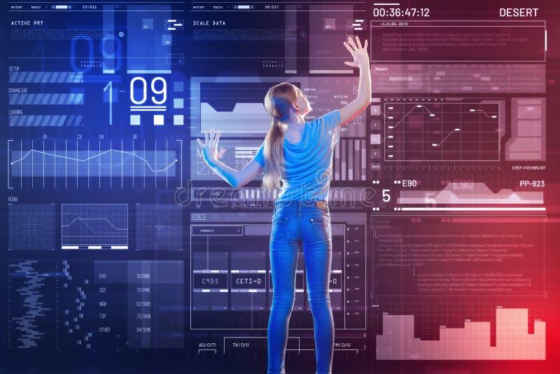 看屏幕的女孩,当探索令人惊讶的现代技术时 免版税库存图片