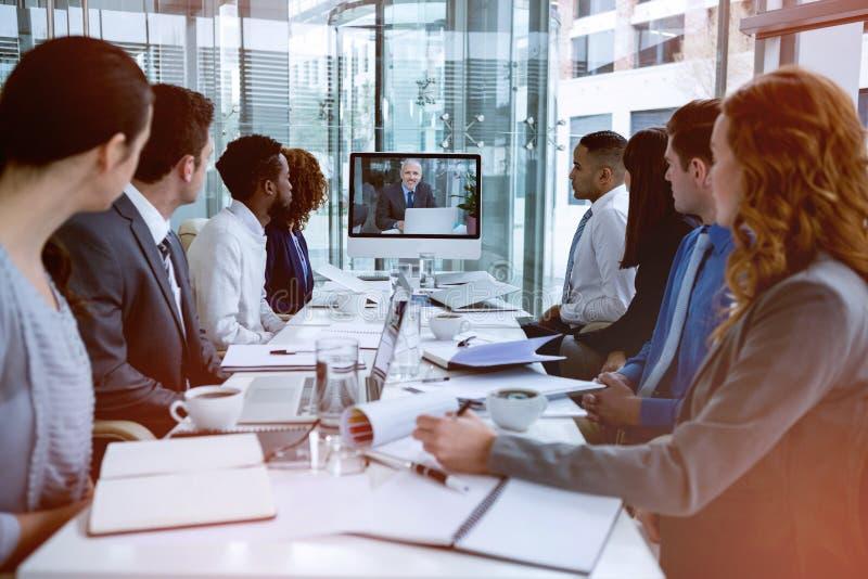 看屏幕的被聚焦的商人在电视电话会议期间 免版税图库摄影