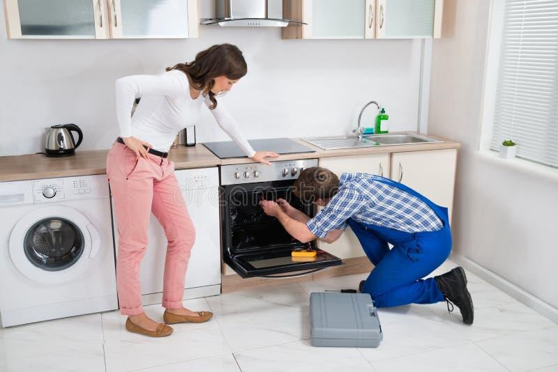 看工作者的妇女修理烤箱 图库摄影