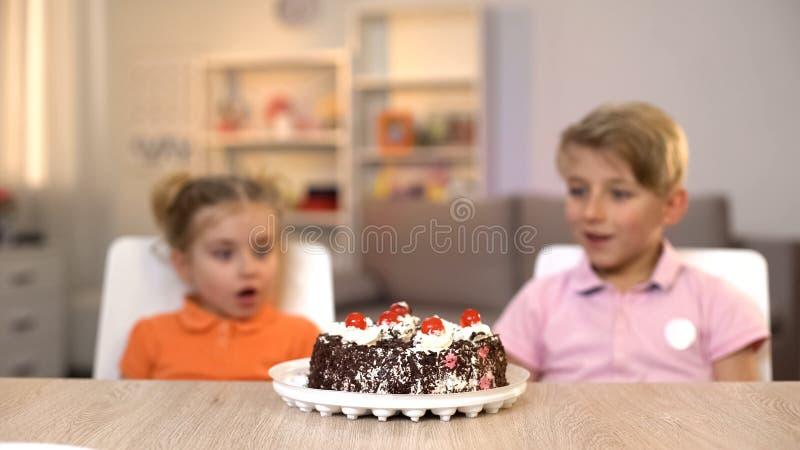 看巧克力蛋糕,生日宴会,爱吃甜品的胃口的惊奇的孩子 免版税库存图片