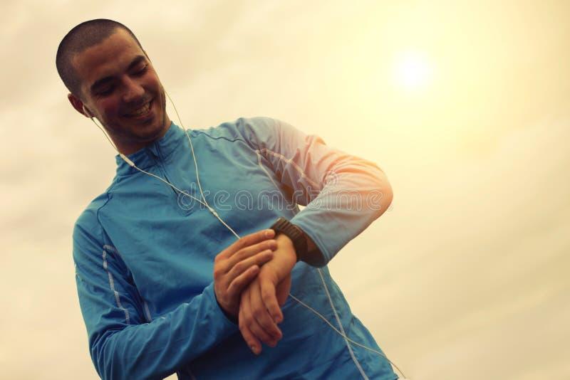 看巧妙的手表的快乐的赛跑者 在表面的重点 免版税图库摄影