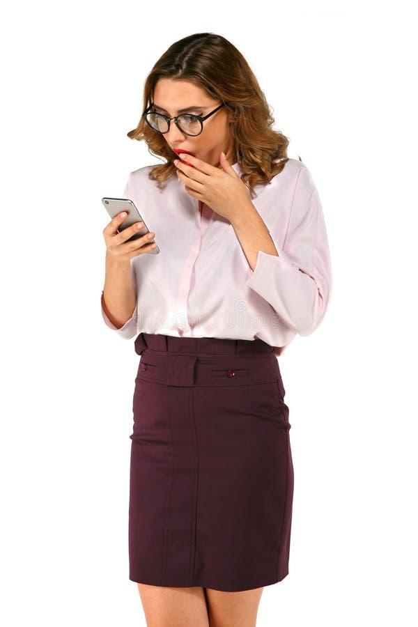 看巧妙的电话的惊奇的女商人 免版税库存照片
