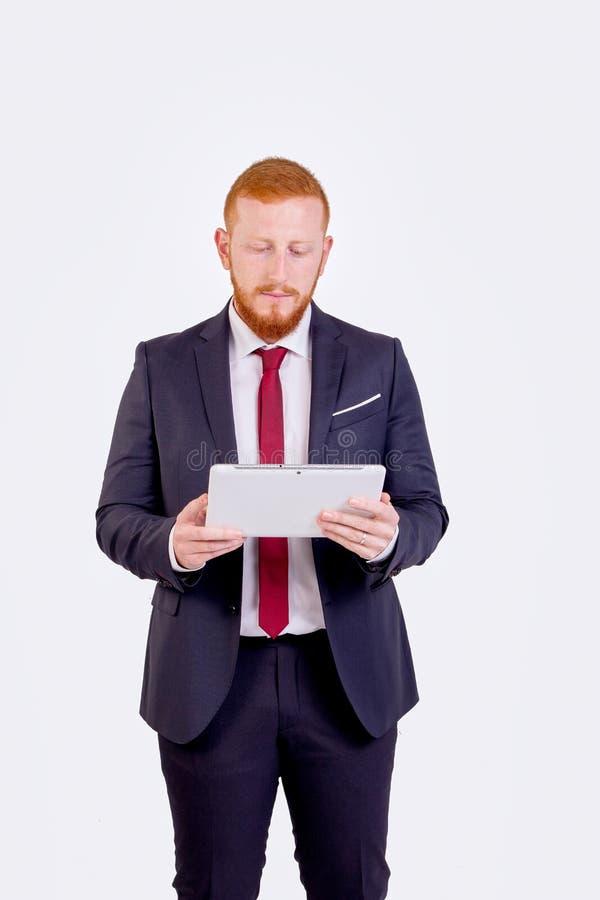 看平板电脑的红头商人 免版税库存图片