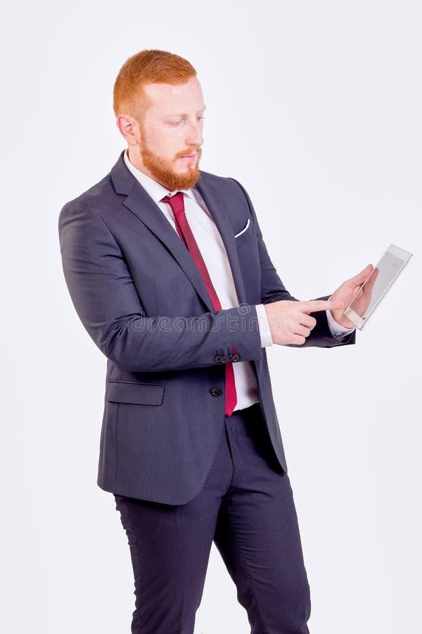 看平板电脑的红头商人 免版税库存照片