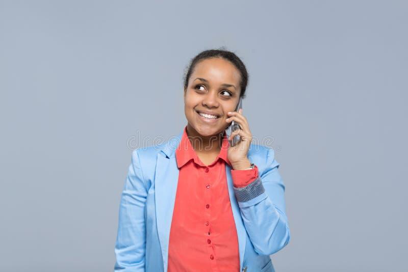 看年轻女商人讲的细胞聪明的电话非裔美国人的女孩愉快的微笑的女实业家复制 免版税库存照片
