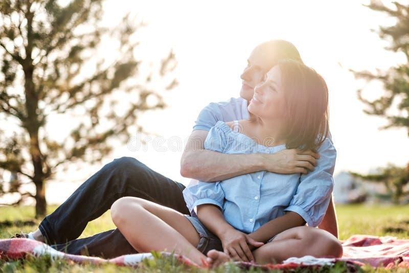看年轻爱恋的夫妇户外坐草,拥抱和  免版税库存图片