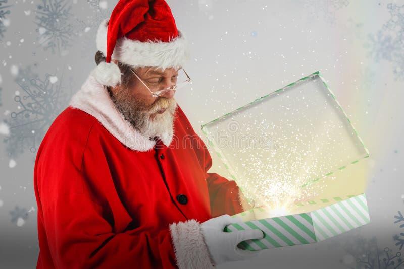 看开放礼物盒的圣诞老人的综合图象 免版税库存图片